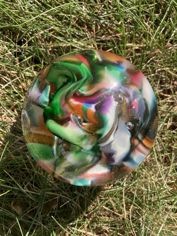 A photograph of a glass globe resting on green and brown grass. The globe contains a riot of swirling colors, including dark and light green, white, burgundy, dark blue, orange and purple.