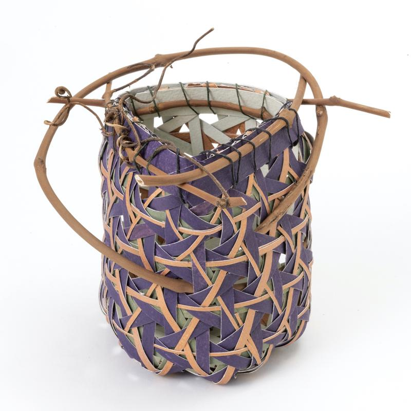 A triangle shaped basket-like vessel made of strips of paper that are hand painted individual colors of purple, mint green and copper.  The strips are woven using a multi-layered hexagonal weave. Peeled grapevine is then attached to the rim with waxed linen thread so the grapevine pierces the piece in 2 places.