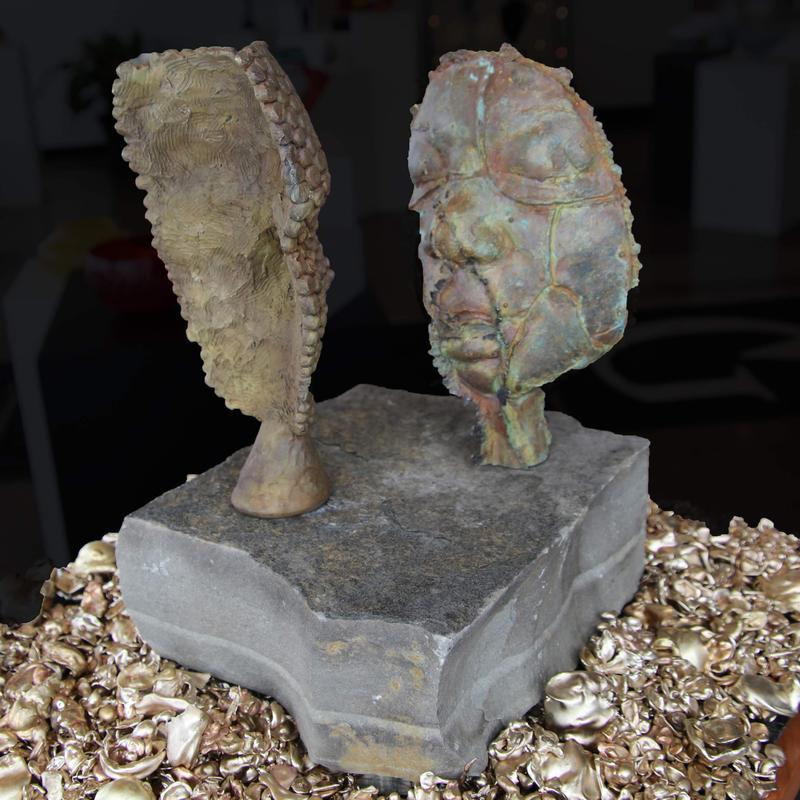 A picture of two bronze faces looking at each other; off set from looking directly at each other. Both faces are sitting on a slab of stone that is floating on blown glass feet. The stone is surrounded by water cast bronze.