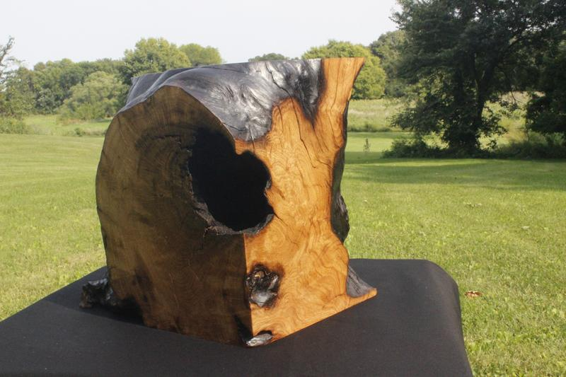 This sculpture was made from an oak burl, the burl was cut to fit into a 12 inch cube. The flat cut surfaces were polished while the natural surfaces were charred with a torch, all surfaces were then oiled to bring out the grain pattern.