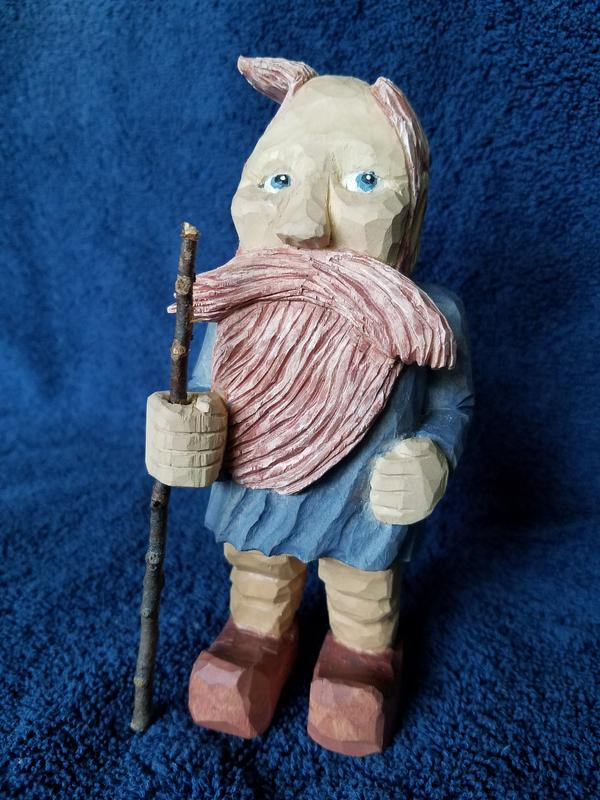 This is a wood carving of Leo standing in the wind with his comb-over hair being blown off his bald head.  He is holding a walking staff and looking off in the direction of the wind.