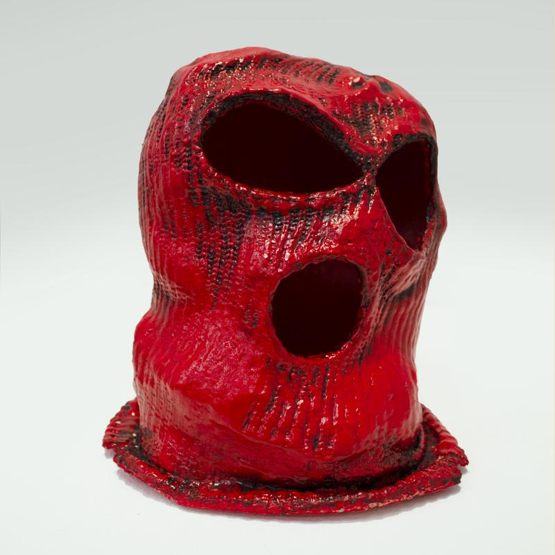 A saturated red balaclava mask sits on a blank white backdrop. The mask is stretched giving the form a large open mouth and eyes.