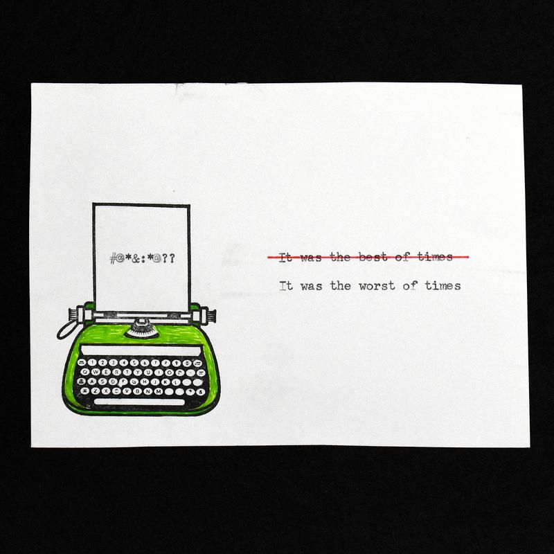 A white four by six inch rectangle on a black felt background. The rectangle shows an ink stamped typewriter, colored green, a grawlix on the page rolling out of the top.  To the right of the typewriter are two typewritten lines.  The top line says It was the best of times, crossed out in red, the bottom line says it was the worst of times.