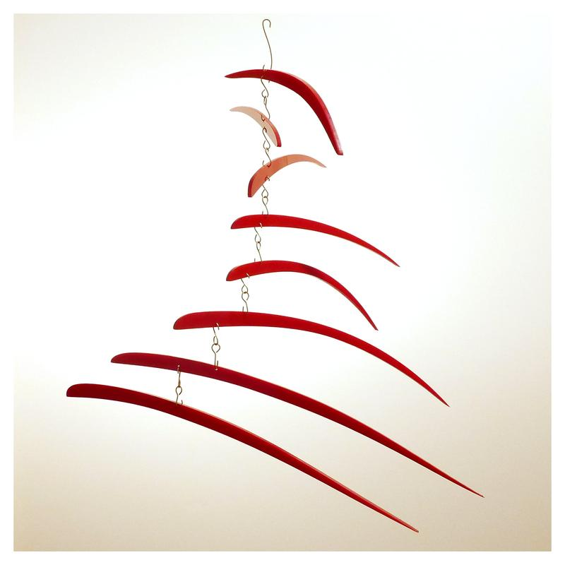 A suspended kinetic sculpture made from red acrylic and brass wire that depicts a fish's flowing pectoral fin.