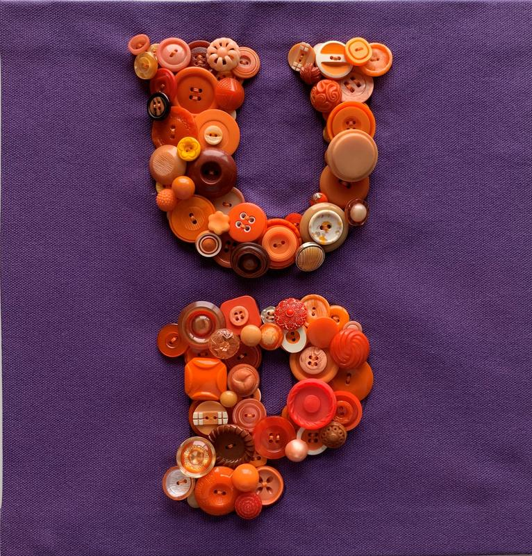 "A collage made of buttons, predominately of orange shades, spelling out the word ""up"" in a broad Goudy-style font hand sewn on purple sail cloth."
