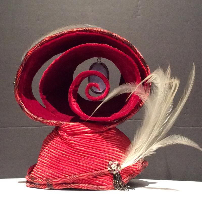 A hat of hand stitched, hand molded cotton buckram with integrated wire foundation covered in silk velvet, nylon cording, fortune pleated satin, silk Dupioni fabric, glass beaded tassels, vintage brooches, sustainably sourced and recycled antique bird of paradise milliners feathers, cut crystal stone,