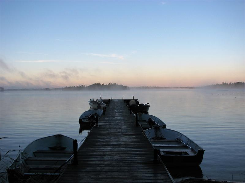Standing at the foot of a dock, fishing boats tied on either side, look out onto a northern Minnesota Lake through the early morning mist as the dawn breaks on the horizon