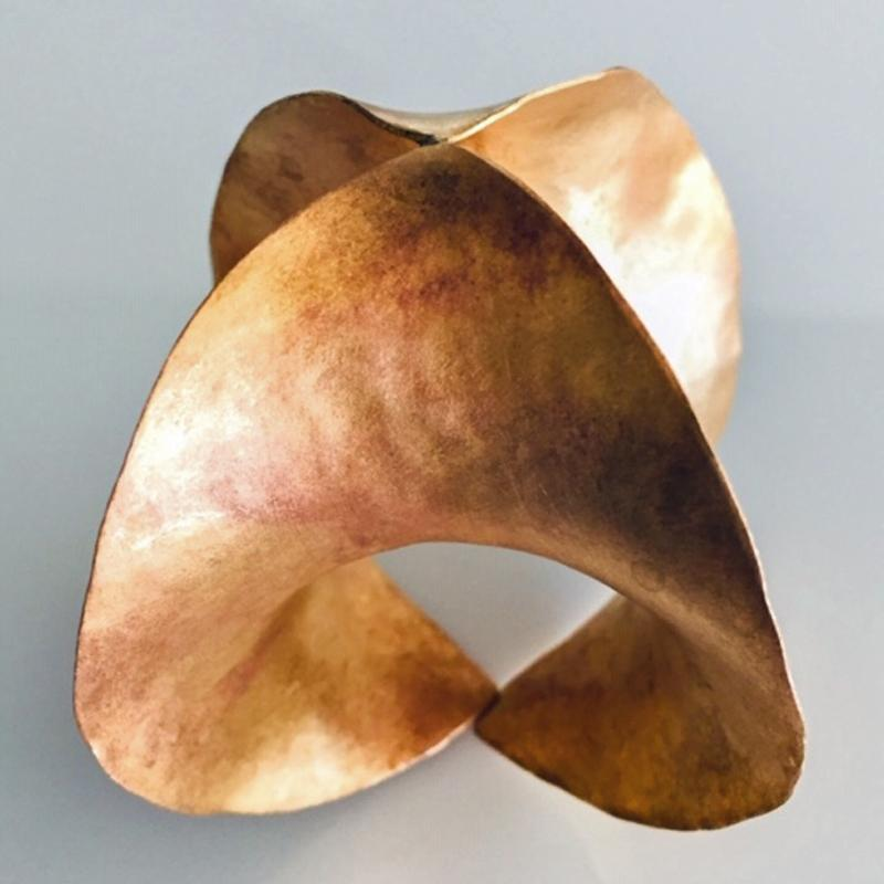 """HPX:  Hyperbolic Paraboloid Extension, An Anticlastic Brass Form  This 3-D brass sculpture started as a flat sheet of 18-gauge brass.  To turn it into a hyperbolic paraboloid or anticlasitc form, the corners are forged over curved stakes along the North-South and East-West axes in opposing directions.  Convex curve along one axis, concave along the other.  The """"X"""" of the HPX describes the way the hammer moves metal from the center of the square outward.  The edges are pulled and stretched and eventually extend enough to meet at diagonally opposite points.  This double curvature shaped shell appears in architecture as a saddle roof.  Despite its rather modern, artistic appearance, this anticlastic shape is highly practical for a roof because it cannot hold water.  To make a synclastic type of form, on the other hand, the axes are moved in the same direction like a bowl or roof gutter.  And, yes, synclastic forms can hold water."""