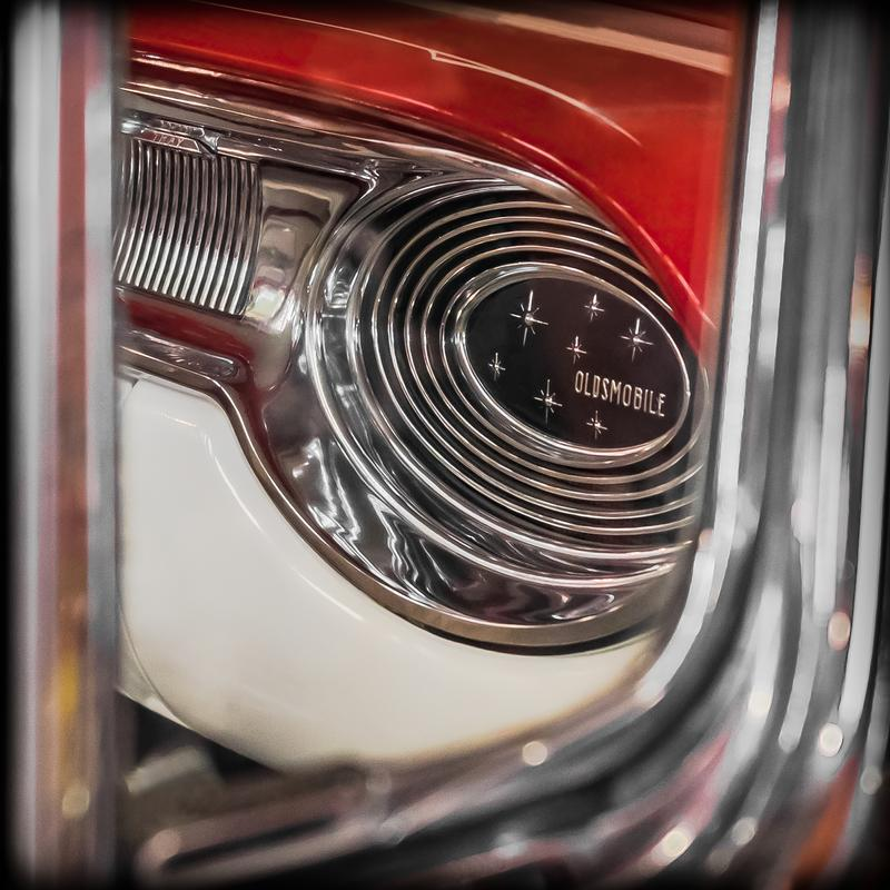 """A photograph looking through the side window to the dashboard of a mid-century automobile with silver chrome trim encircling the word """"Oldsmobile"""" and red and white above and below. The chrome around the window provides a partial frame."""