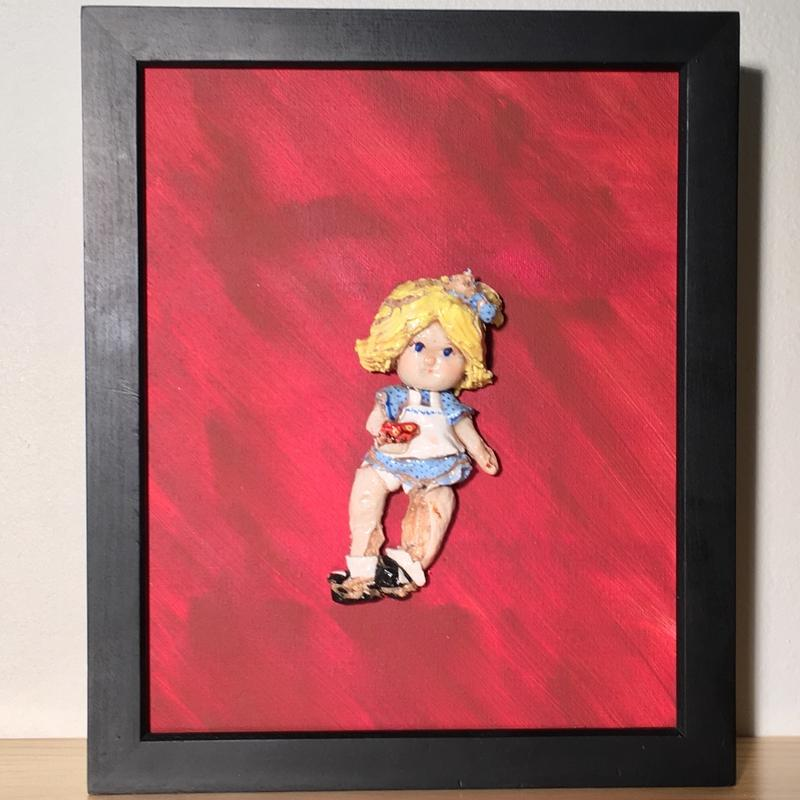 A red painting in a black frame, a girl with yellow hair with broken legs, in a blue dress holding a red flower.