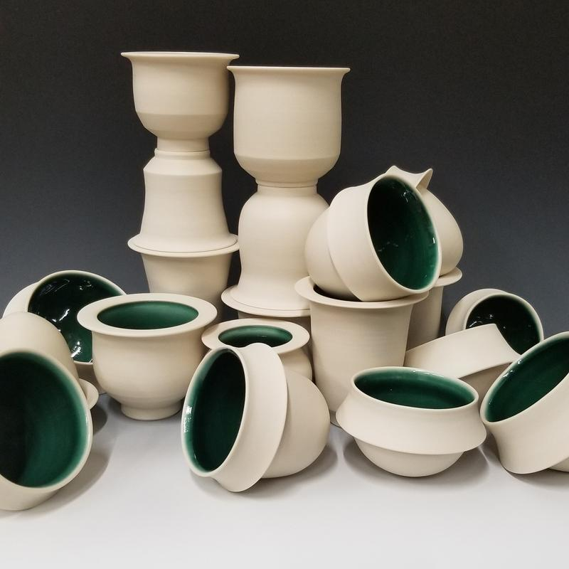White porcelain cups with a bright green inside stacked on each other to form a random pile.