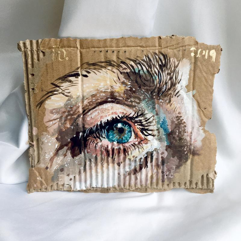 A detailed painting of a man's eye looking to the right on a piece of ribbed cardboard. Pink, orange, peach, and blue tones make up his skin with dark brown lashes and eyebrow hairs.