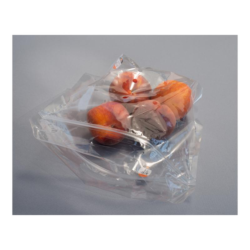 Still Life Photograph: Four peaches in plastic bag with reflected light and price tag on light gray background.