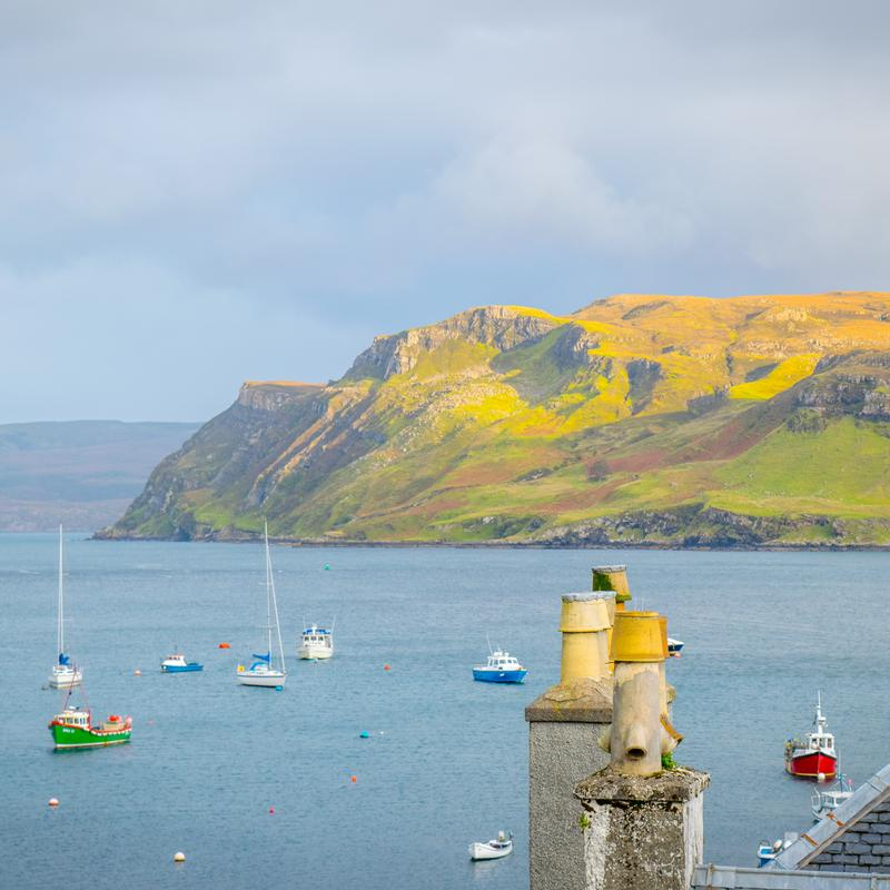 Over looking the beautiful Harbor of Portree, Isle of Skye, Scotland in Autumn. Blue sea water, lime green mountain dappled in sunlight. Sail boats along with the locals fishing boats dot the water. Rooftop chimneys highlight the scene.
