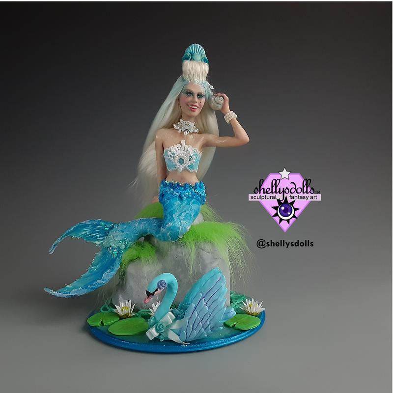 A mermaid with blue eyes and long blonde hair holding a shell up to her ear. She has a blue tail covered in white lace. She is wearing pearls and blue shells. A decorated white and blue lace top. She sits atop a gray rock with a blue swan floating by her amidst water lilies.