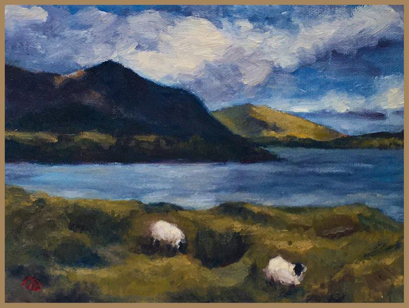 A picture of two sheep on a green grassy knoll bordered by an inlet of the Atlantic Ocean and a Irish landscape backdrop.