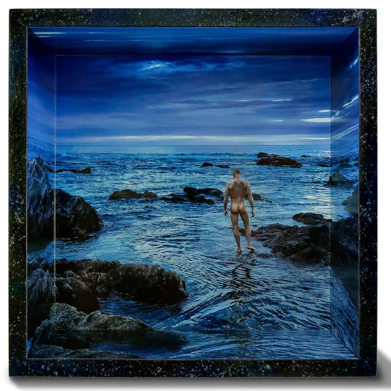 Color photograph overlooking a wide expanse of ocean at twilight, within a dramatic landscape entirely shrouded in deep dark blue hues, we find a naked male figure walking out into the waters of the unknown. The photo is mounted within a shadowbox frame with the image continuing and wrapping around the inside of the shadowbox frame, which is hand-painted in black with subtle hints of blue and cosmic wonder.
