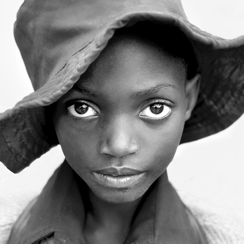 This is a Black and White photograph of a young African school girl on a white back ground which is a dirt road. Her eyes are quite large and stare out from the brim of her hat.