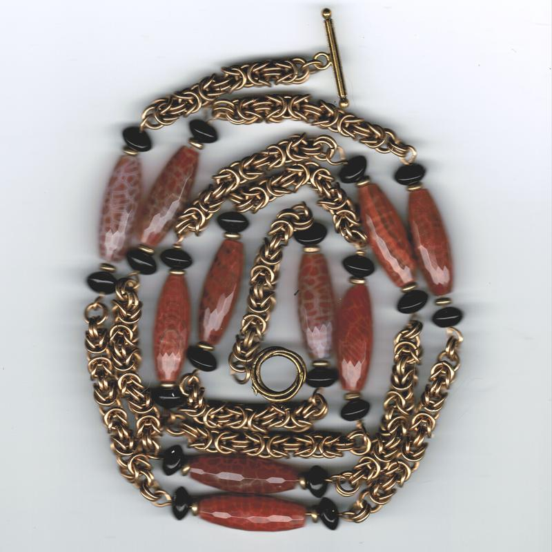 This is a red brass necklace composed of large orange crackle agate rice and black onyx rondelles, nestled between byzantine weave section.