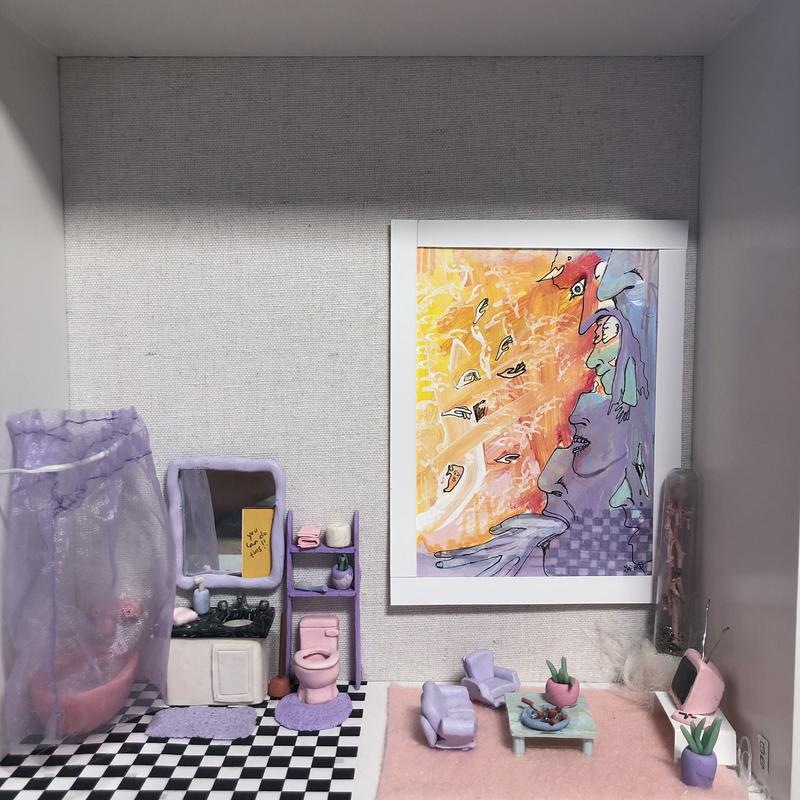 """A miniature pastel bathroom scene sits in a shadow box with a mini pink toilet, sitting on checkerboard tile, with a pastel purple toilet matt.  There is a mirror above the sink with a written sign saying """"you can do this!!!""""  The sink counter has a miniature soap and hand towel.  There is a shelf above the toilet with mini bathroom items such as toilet paper, a tooth brush and bath towels, all in pastel tones.  Next door to the bathroom is a living room with two pastel purple couches sitting around a baby blue coffee table that has an overflowing miniature ash tray and a house plant.  The couches are facing a pink tv that is sitting on a white modern TV stand.  There is a framed large painting on the wall that features abstract faces, checkerboard patterns, and a backround of warmer tones.  All of the furniture sits on a baby pink felt rug.  There is a decorative abstract lamp in the corner."""