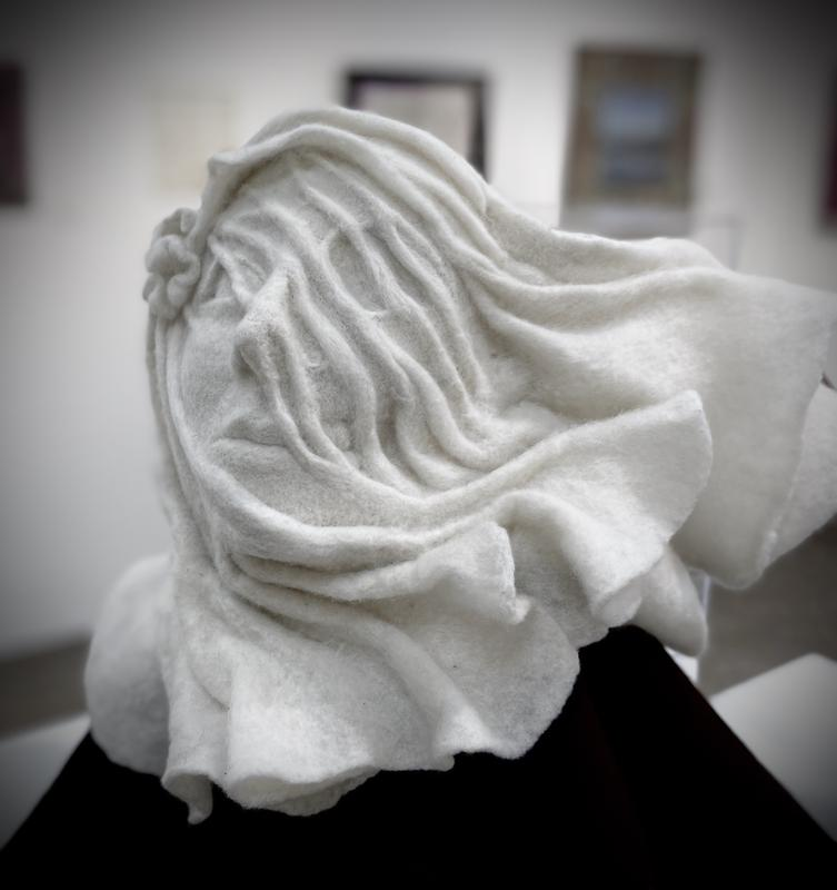 A sculpted bust of a veiled woman made from wool that looks like marble. The wind appears to be blowing the fabric against her face and the rest is billowing away from her. The veil reveals beneath the illusion of translucent folds half of her face is classicly beautiful and the other half is her skull.