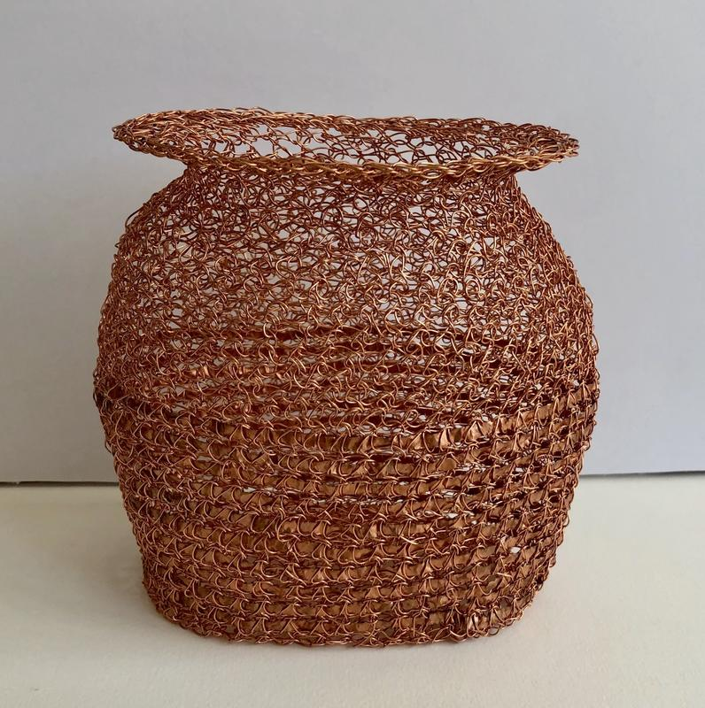 Oval shaped vessel of crocheted with copper wire over narrow copper strip.