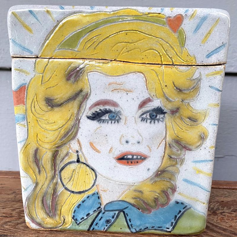 "A Ceramic Box with an etched drawing of Dolly Parton. The top has the name ""Dolly"" etched in cursive. The other 3 sides feature a guitar, rainbows and flowers"