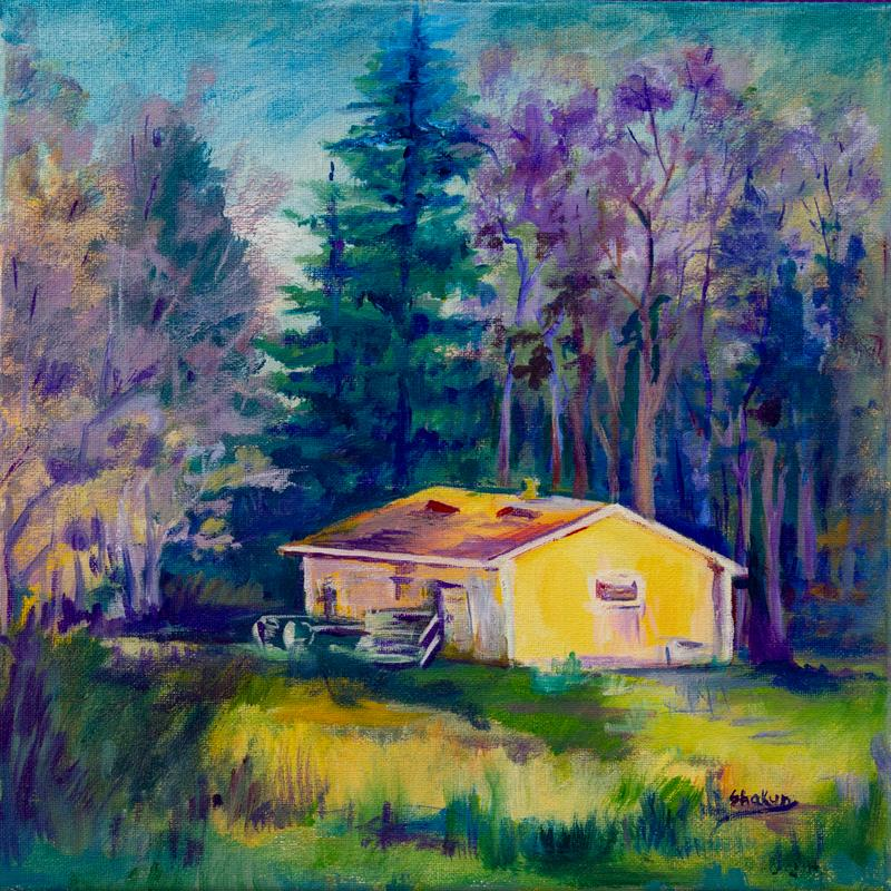 Evening light is shining on a small yellow building and casting a warm glow. It is surrounded with various tall trees and evergreens. Purple and pink hues of the evening light, blues and greens of the trees, contrast with the warm yellows of the building.  This backyard scene gives the impression of a cabin in the woods; peaceful, serene and warm