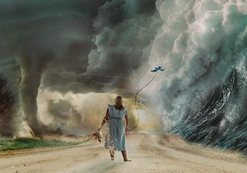 The color theme is muted greys and blues, brown, tan and dark green. A girl on a dirt road facing away from the viewer.  She is in a simple blue cotton dress that is blowing in the wind and she has a strong grounded stance.  Ahead of her, down the dirt road, are multiple severe weather elements.  To the right of the dirt road is a tsunami where the wave is just about to crash down on the edge of the dirt road and onto her.  The wave goes all the way to the sky where the white caps start to build up into large white storm like clouds that cover the middle of the top frame.  The clouds direct your eyes to the left side of the picture where there is lighting and a tornado to the edge of the left side of the road.  The tornado is kicking up dirt and grass, the wind from the tornado is blowing her dress and it is starting to take part of her leg as you her left leg is disintegrating like sand towards to the tornado.  The girl continues stand strong, she is holding a bottle of wine and raggedy Anne doll in her left hand.  In her right hand she is holding a leash that is attached to a blue bird that looks to be her guide or attempting to fly free.