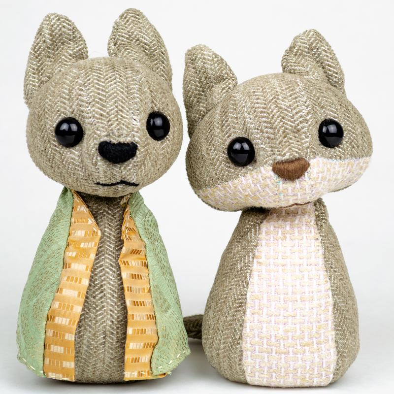 Two small stuffed animals made of neutrally-toned wool sit together. One wears a green silk cloak with orange trim.