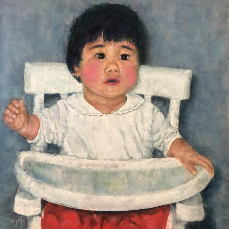 A portrait of a 2 year old Chinese girl with rosy cheeks in a high chair wearing a white shirt and red pants with blue background, who looks like she's asking a question.