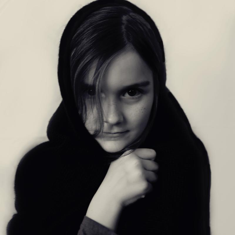 Black and white photo of a girl holding a black scarf wrapped around her head.