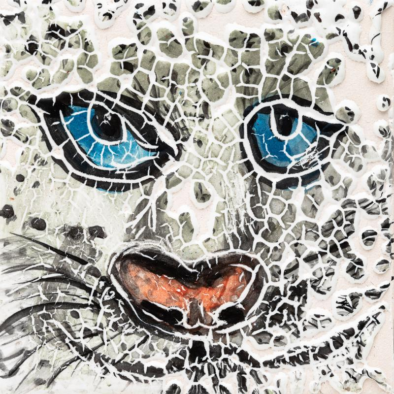 Close up face of a snow leopard. They blue eyes and orange nose are prominent features. The glaze has crackled away creating an abstract of the black and white spotted fur.