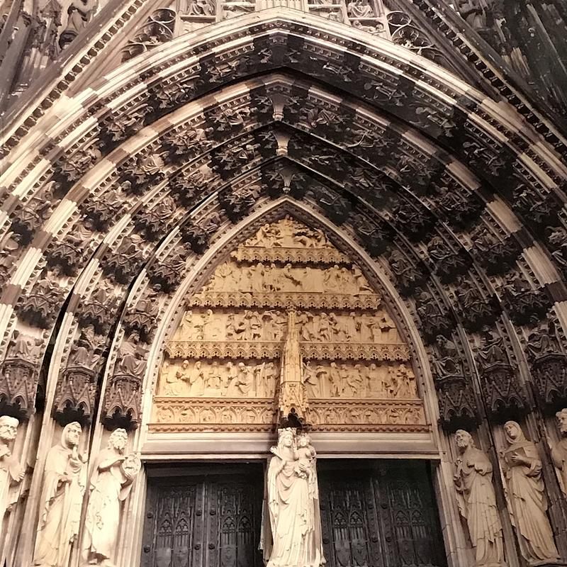 A 3-D image of the highly carved multiple arched, grey natural stone entryway to a Gothic Cathedral.  Each arch has a contrasting white statue at its base and the Madonna and Child overhangs the central iron doorway.
