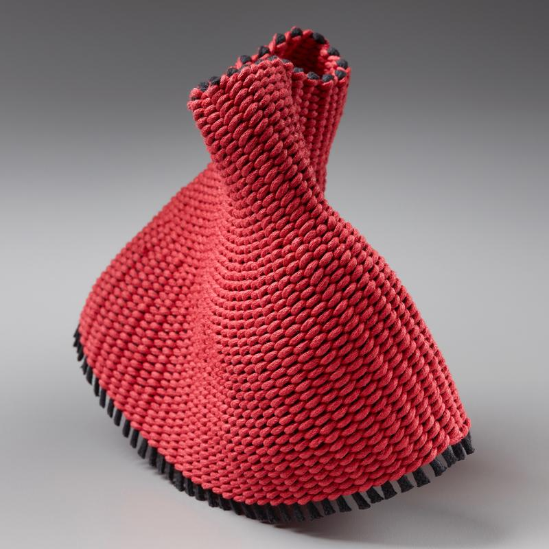 A red twined weaving reflective of a dancer. Made with cotton.