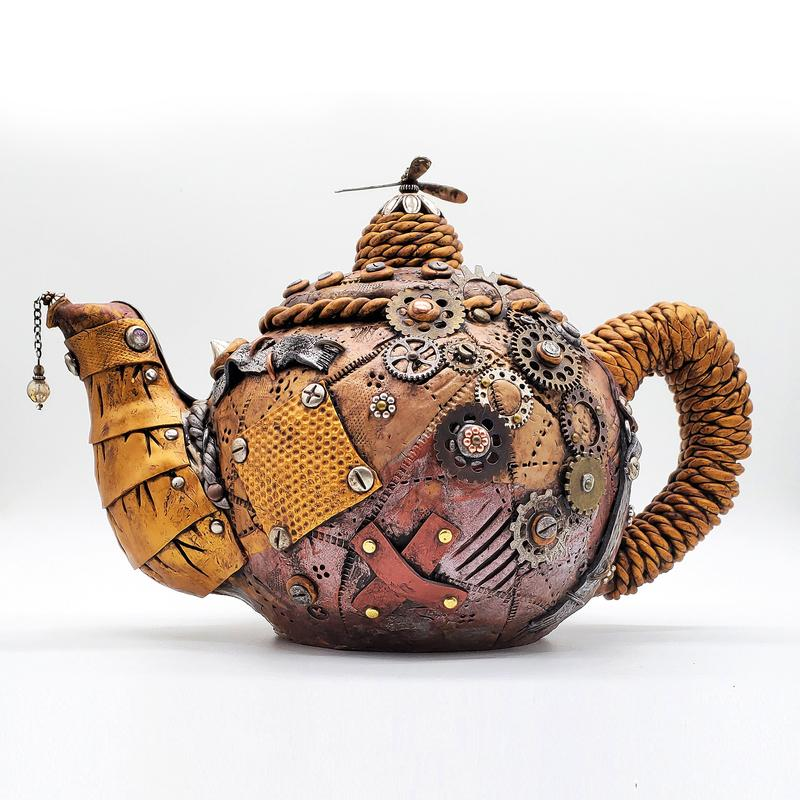 A teapot styled in a metallic and leather steampunk facade with straps, whirly-gigs, chains, ropes and gears.