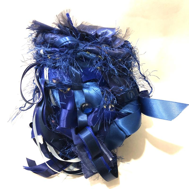 slightly elongated ball shaped soft sculpture, various shades of blue, textured fabric and smooth ribbons are woven together like a basket.