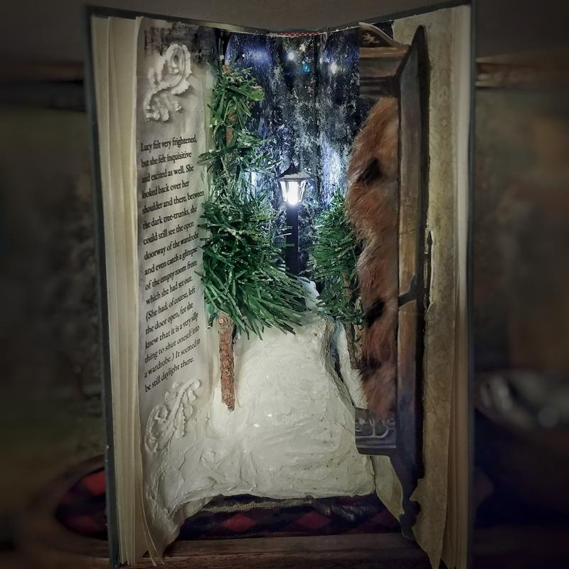 An altered book opened to reveal a lighted lamppost on a hill of snow beyond miniature pines and a section of wardrobe.
