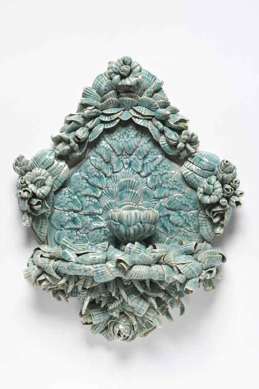 Blue textured wall piece ornate w flowers and presenting centrally locates blossom cup