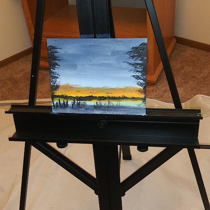 A painting of a lake at night with sunset reflecting trees and water meeting the orange glow of dusk ....