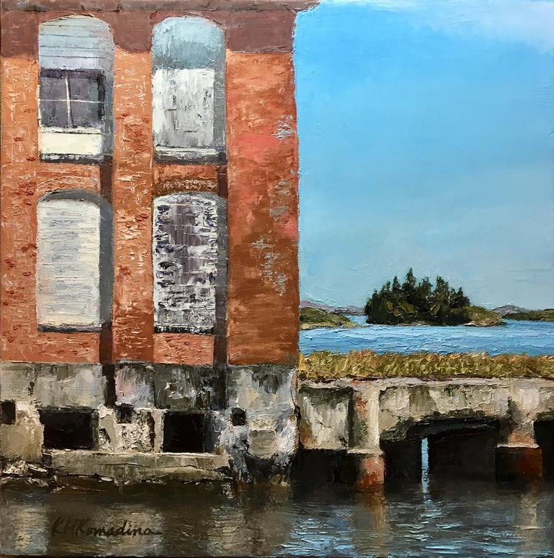 A boarded up sardine cannery on the coast of Maine,  weathered red brick with four boarded up windows supported by concrete pylons in the water.