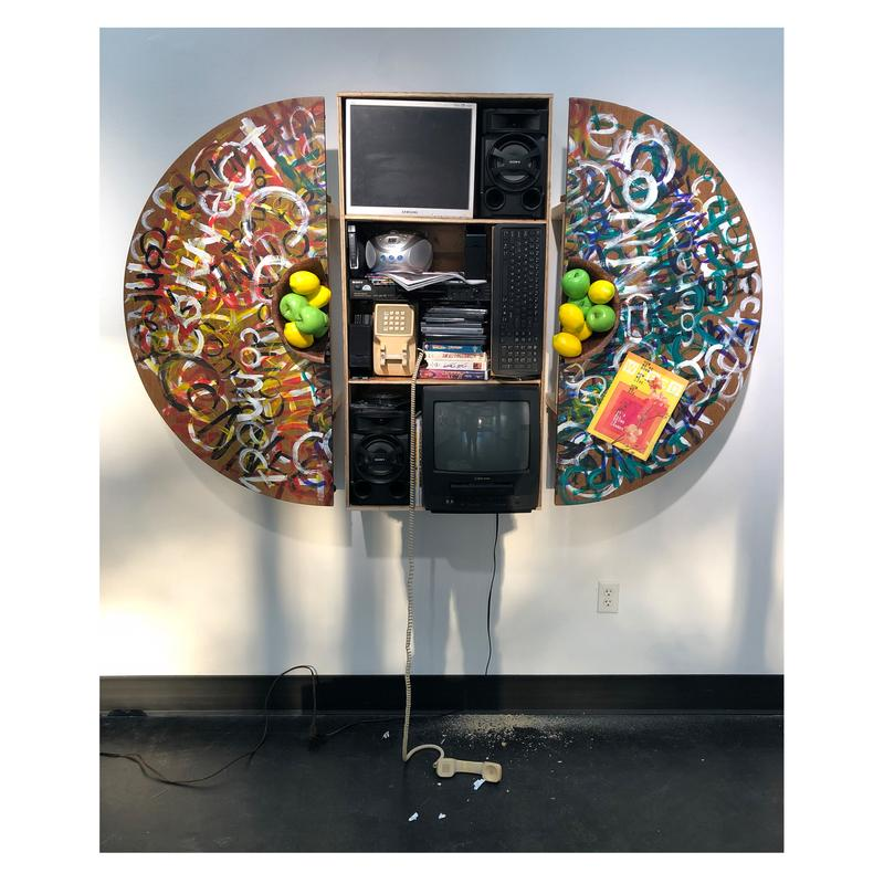 """This photograph depicts a sculpture built of a dinner table and bowl of apples and lemons cut in half and mounted to a wall. Atop the surface of the table can be seen the word """"Connect"""" painted chaotically in repetition. Between the halves is a collection of household multimedia (computer, tv, vas/DVD player, DVDs, CDs, magazines). There is a telephone hanging off the hook and the shadow of an individual gets lost into the cluttered objects in the middle of the split table."""