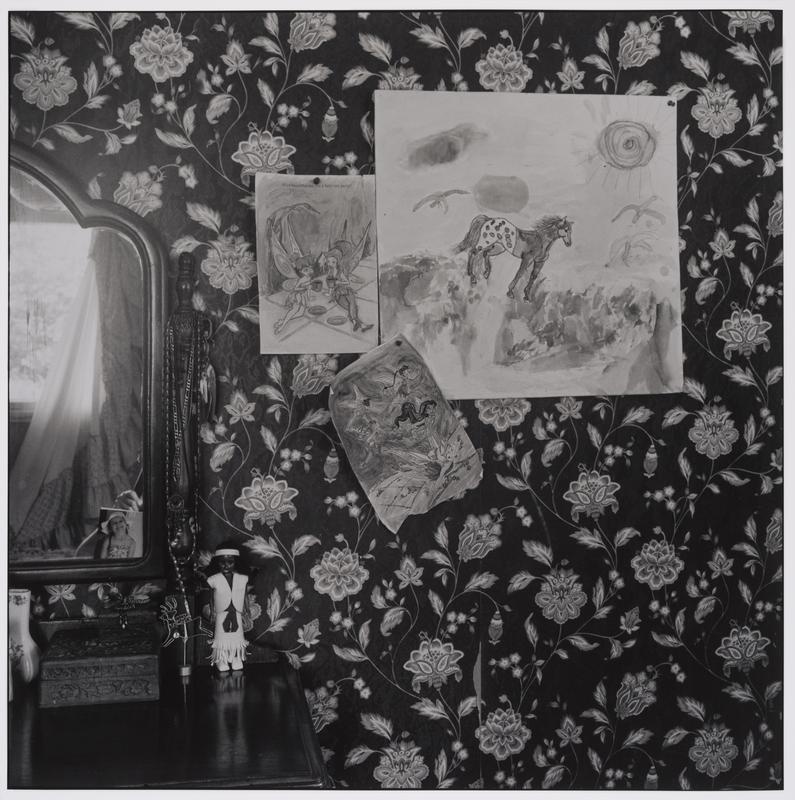 This is a black and white photograph of Autumn's room. On the left side is a dark wood mirrored dresser against a robust floral wallpaper of large undulating white flowers, leaves and vines against a dark background. Tacked into the wall to the right of the dresser are three pinned images, two smaller images are from a children's coloring book and picture fairies. The larger image is drawn by hand, water colored and features a horse within a sunny landscape.