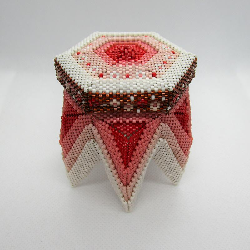 A beadwoven box with six legs shading from cream to pink to red. The lid is a hexagon in the same colors with a brown band around the edge.