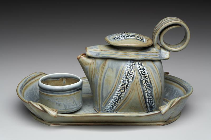 A small teapot, cup and tray in shades of blue, designed to create a moment of peace and contemplation.