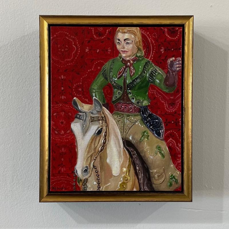 A painting of a vintage toy horse and cowgirl against a red bandana background.