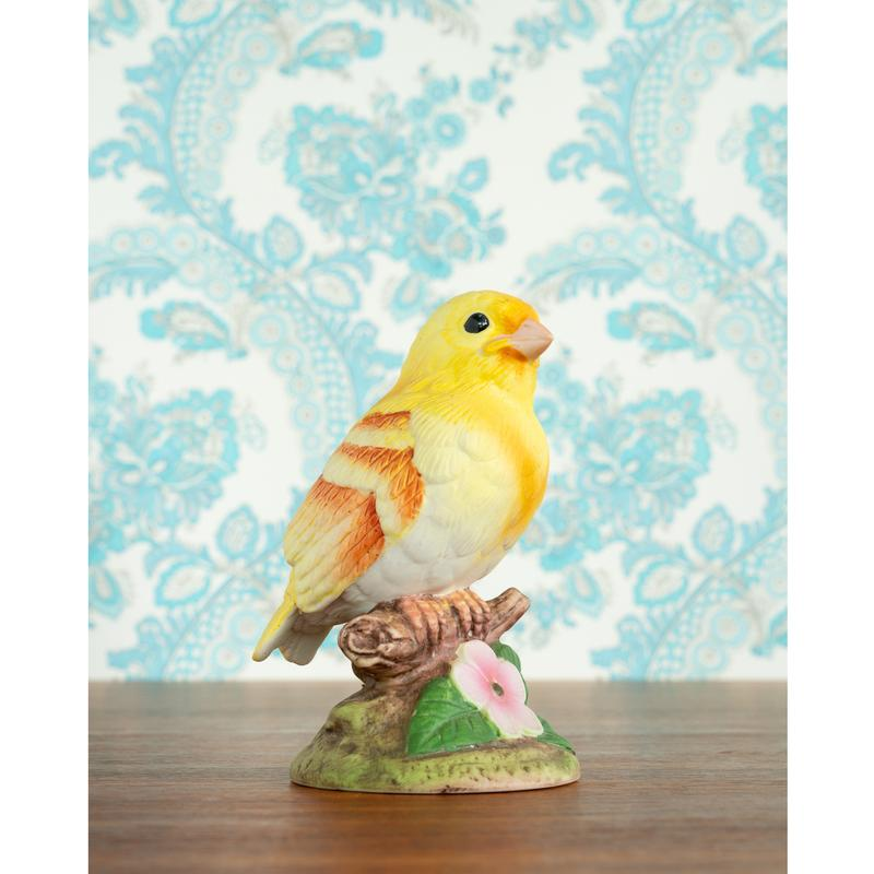 A bright yellow ceramic bird is in front of a blue and white paisley backdrop.