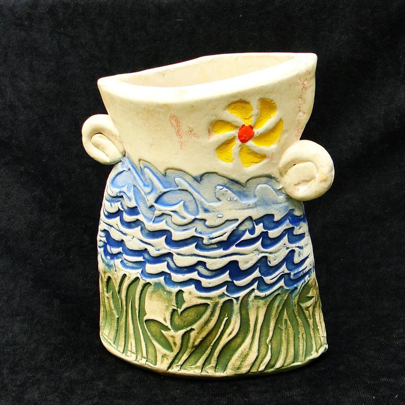 Irregularly shaped stoneware vase with two spiral handles.  Textured, brightly colored surface evoking undersea, sea, sky and sun.
