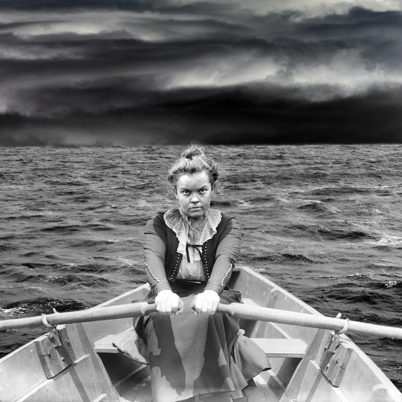 Black and White Photomontage of a determined woman rowing a boat across Lake Superior with ominous clouds ahead.