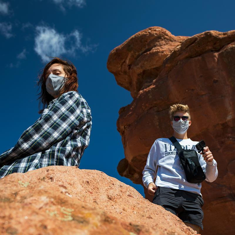 A color photograph of a man standing and a woman sitting around large orange boulders with a partly cloudy, deep-blue sky in the background. The photo is taken from a low vantage point with both subjects partially behind the boulders. Both subjects are wearing masks and social distancing.